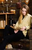 Girl student study with book in house of gamekeeper. Study concept. Girl in casual outfit sits with book in wooden. Vintage interior. Lady on calm face in plaid royalty free stock photos