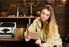 Girl student study with book in house of gamekeeper. Girl in casual outfit sits with book in wooden vintage interior. Study concept. Lady on calm face in plaid royalty free stock image