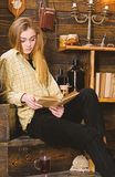Girl student study with book in house of gamekeeper. Study concept. Girl in casual outfit sits with book in wooden. Vintage interior. Lady on calm face in plaid stock photos