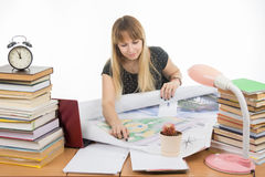 Girl student studying design drawing master plan at table cluttered with books Royalty Free Stock Photo