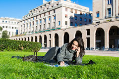 Girl / student studying / smiling on a green grass lawn Stock Image