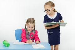 Girl student teacher dictating dictation. Two girls play school teacher and student Royalty Free Stock Images