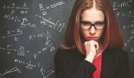 Girl student, the teacher writes on  blackboard chalk formula Stock Image