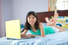 Girl student using laptop in bedroom Royalty Free Stock Photo