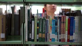Girl student walking between shelves, searching for books stock footage