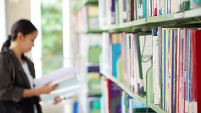 Girl student walking between shelves, searching for books stock video footage
