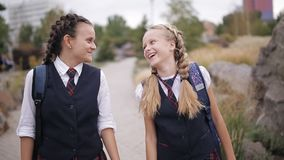 Girl student wearing the same school uniform with backpacks walk through the Park laughing and talking stock footage