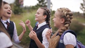 Schoolgirls having fun after school on the street. Girl student wearing the same school uniform laughing and singing stock footage