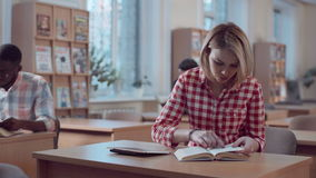 Girl student working with book and tablet stock video footage