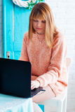 A girl student working with laptop. Girl freelancer with a computer in a home interior. Woman online buyer looks at the Stock Photo