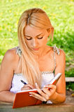 Girl-student writes. Beautiful smiling girl-student writes to writing-books against green summer nature Stock Images
