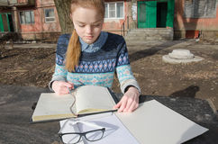 Girl student writing work. Carroty girl student writing homework outdoor the sunlight Stock Image