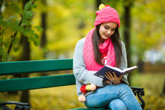 Girl students read book in yellow autumn park. Young happy girl students read book in yellow autumn park Royalty Free Stock Images