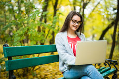 Girl students working on laptop in autumn park Stock Photography