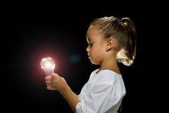 Girl in studio holding lightbulb stock image