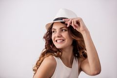 Girl in the studio. Portrait of a happy young girl with a hat on a white background smiling at the camera stock photos