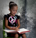 Girl in studio reading a book. Young girl sitting in a studio chair with a grey background. She is reading a book stock images