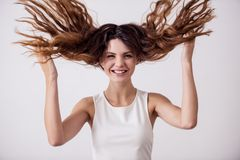 Girl in the studio. Young pretty girl on a white background playing with her hair. Shooting in the studio stock photo