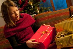 Girl studying christmas gift Stock Photos