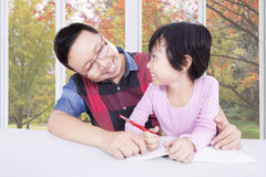 Girl studying with dad near the window Stock Photo