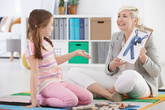 Girl studying difficult letters. With speech therapist Stock Image