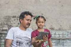 A girl studying elementary education in open school. Unidentified person in ludhiana, punjab, india helping his unidentified daughter in study through digital royalty free stock image