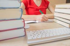 Girl studying. Girl doing her homework. School books on desk, education concept. Young Girl studying. Girl doing her homework. School books on desk, education Stock Photography
