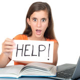 Girl studying holding a sign with the word HELP. Teenage girl studying and holding a sign with the word HELP Stock Image