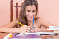 Girl studying at home and smiling. Hispanic girl studying at home and smiling royalty free stock photography