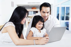 Girl studying with laptop and her parents royalty free stock image