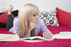 Girl Studying While Lying On Bed Royalty Free Stock Images