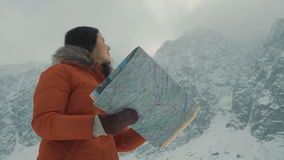 The girl is studying a map against the background of snow-capped mountains. Girl is studying a map against the background of snow-capped mountains. Searches his stock video footage