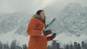 The girl is studying a map against the background of snow-capped mountains stock video footage