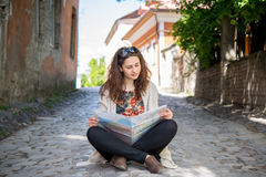 Girl studying a map while sitting on the ground Royalty Free Stock Photos