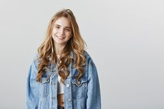 Girl studying new language with audio lessons. Good-looking happy female model with blond hair in denim jacket, wearing. Earphones and smiling broadly at camera Royalty Free Stock Images