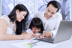 Girl studying with parents at home Royalty Free Stock Image