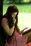 Girl studying in the park. Attractive girl with long hair is studying in the park Stock Image
