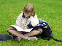 Girl studying in park. Blond girl sitting in grass studying royalty free stock image