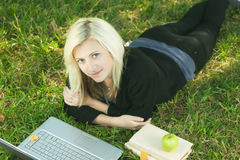 Girl studying in park with laptop Royalty Free Stock Photos