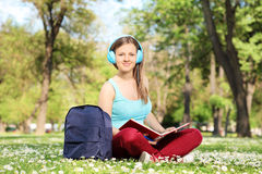 Girl studying in park and listening to a music Royalty Free Stock Photos