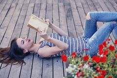 Girl studying and reading a book. Relax, rest, education concept, recreation . Young attractive girl studying and reading a book on a wooden floor . Relax, rest Stock Images