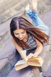 Girl studying and reading a book. Relax, rest, education concept, recreation . Young attractive girl studying and reading a book . Relax, rest, education Royalty Free Stock Photography