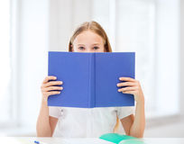 Girl studying and reading book at school Royalty Free Stock Image