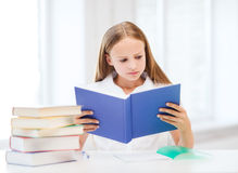 Girl studying and reading book at school Stock Photos