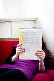 Girl studying at university. Young girl reading notes on a couch royalty free stock photography