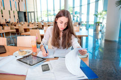 Girl studying in the University canteen Stock Photos