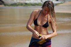 Girl with a stunning figure and wet hair after bathing removes suit for surfing Stock Image