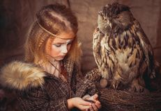 Girl in the style of boho with an owl. Boho chic hugs big owl stock photo