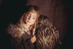 Girl in the style of boho with an owl. Boho chic hugs big owl stock photos