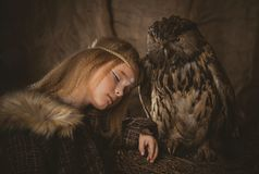 Girl in the style of boho with an owl. Boho chic hugs big owl royalty free stock photography